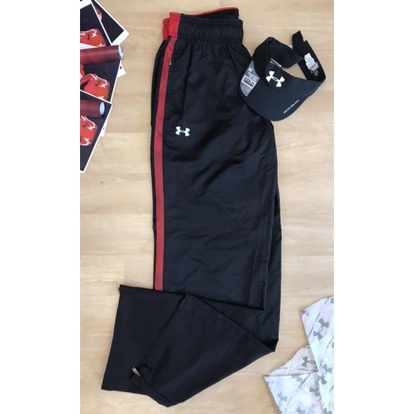 Photo of Women's Under Armour Windbreaker pants in size Medium Loose fit, and a Women's St. John's visor